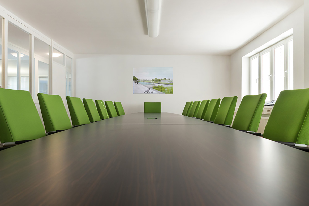 Konferenztisch mit grünen Stühlen