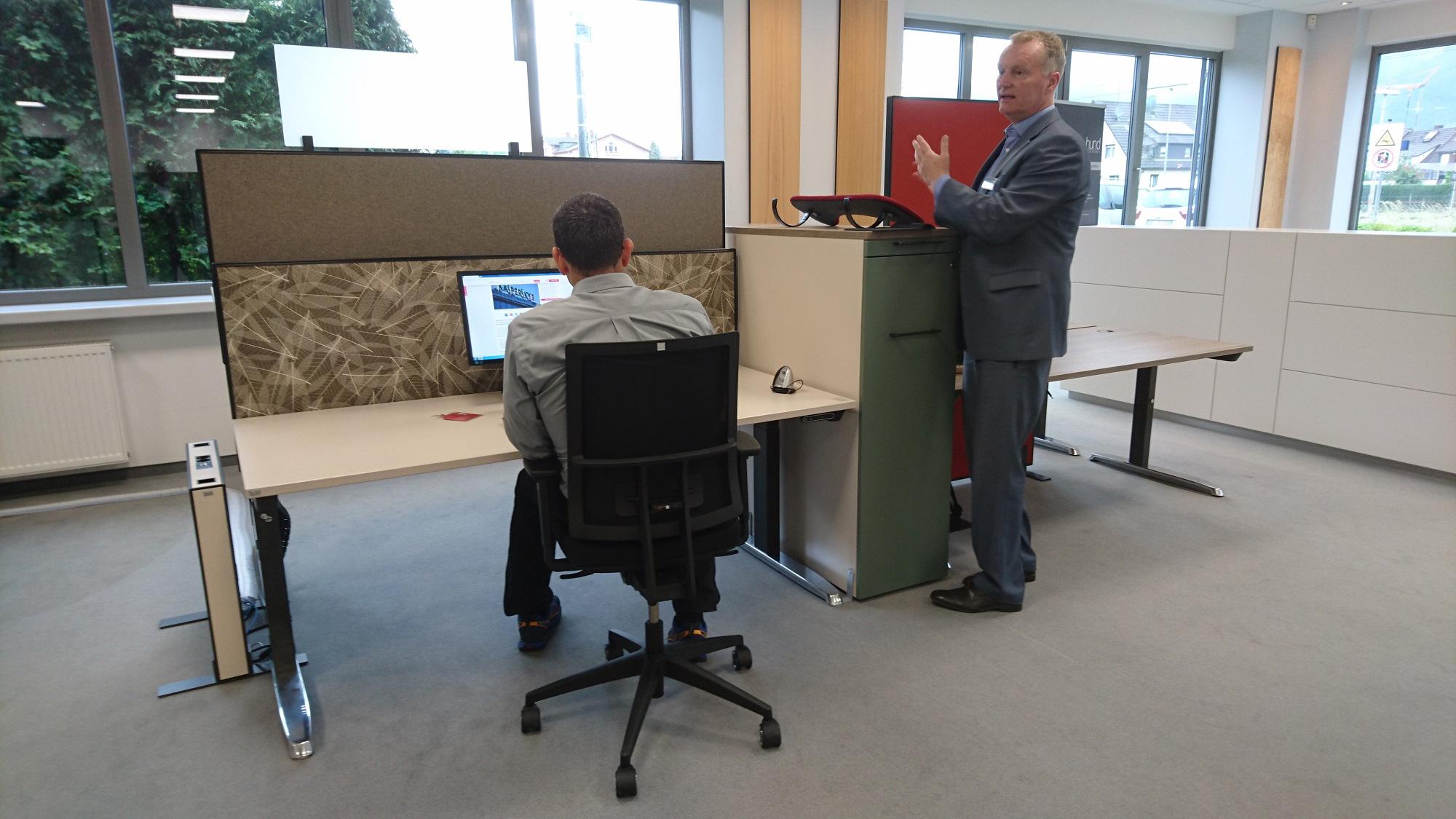 Mitarbeiter am Steh-Sitz-Arbeitsplatz. Herr Brunner geht auf die Haltung des sitzenden Mitarbeiters ein.